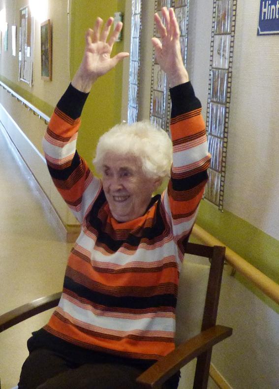 Eine Senioren sitzt auf einem Stuhl und streckt die Hände in die Höhe.