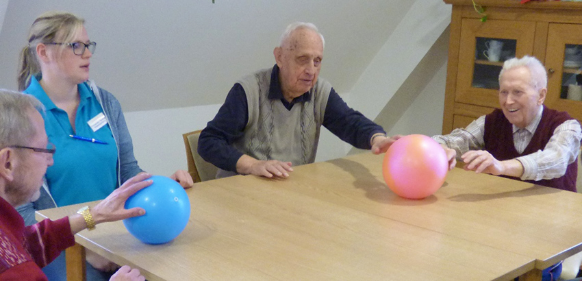 Senioren rollen zwei farbige Bälle über den Tisch.