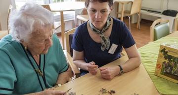 Ergotherapeutin beim Puzzeln mit einer Bewohnerin