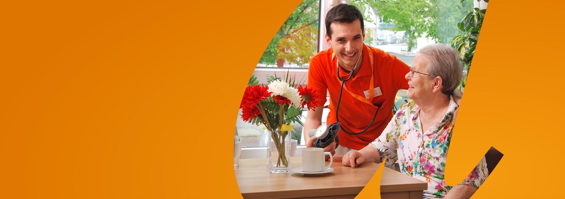 Relocation Management: Ein ausländischer junger avendi-Mitarbeiter, der nach Deutschland umgezogen ist, hat einer Bewohnerin den Blutdruck gemessen.