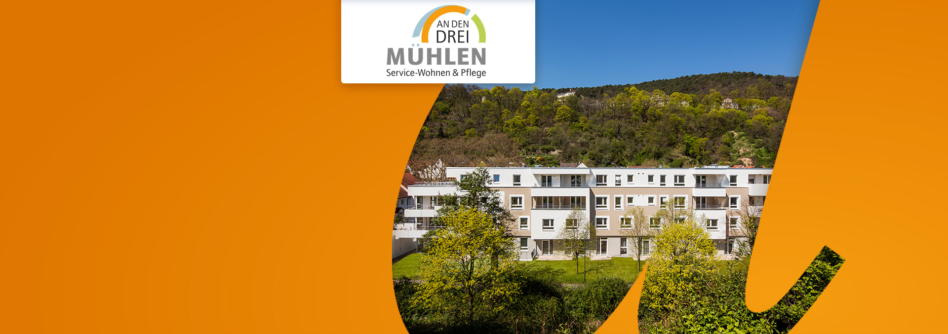 Service-Wohnen und Pflege An den drei Mühlen: Blick von außen über Büsche und Rasen auf die Einrichtung, im Hintergrund Wald.