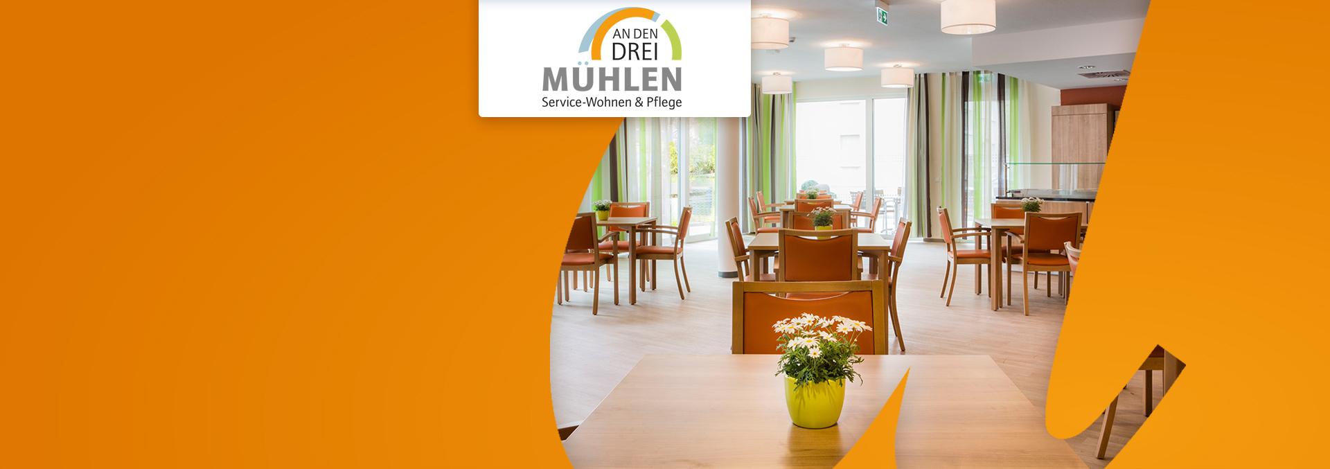 Service-Wohnen und Pflege An den drei Mühlen: Helle Cafeteria, Parkett sowie Tische und Stühle aus mittel-hellem Holz, auf den Tischen Blumenvasen.