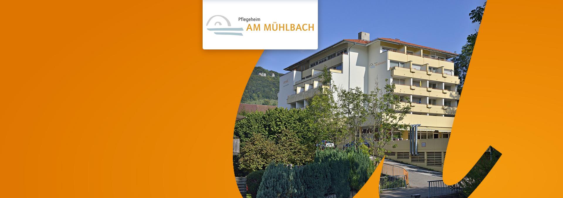 Pflegeheim Am Mühlbach von außen, Auffahrt zur sechsstöckigen Einrichtung, gesäumt von Büschen und Bäumen.