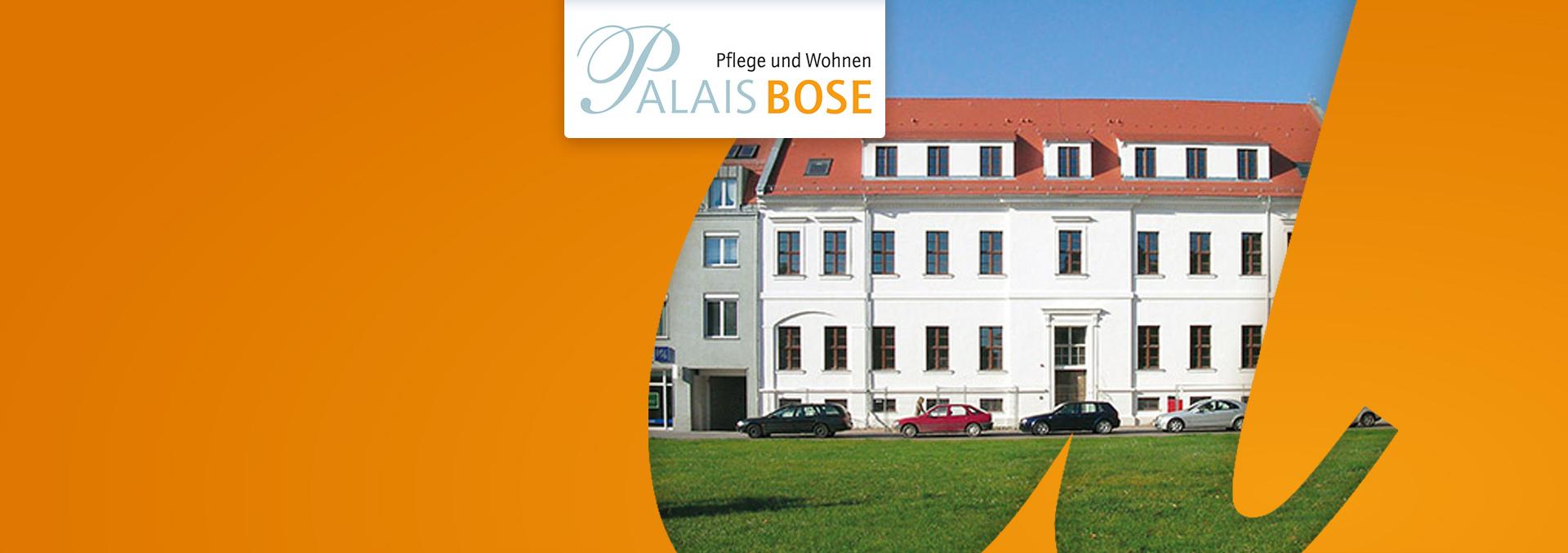 Pflege und Wohnen im Palais Bose: Rückansicht des weißen Gebäudes mit Autos davor, über eine Wiese fotografiert.