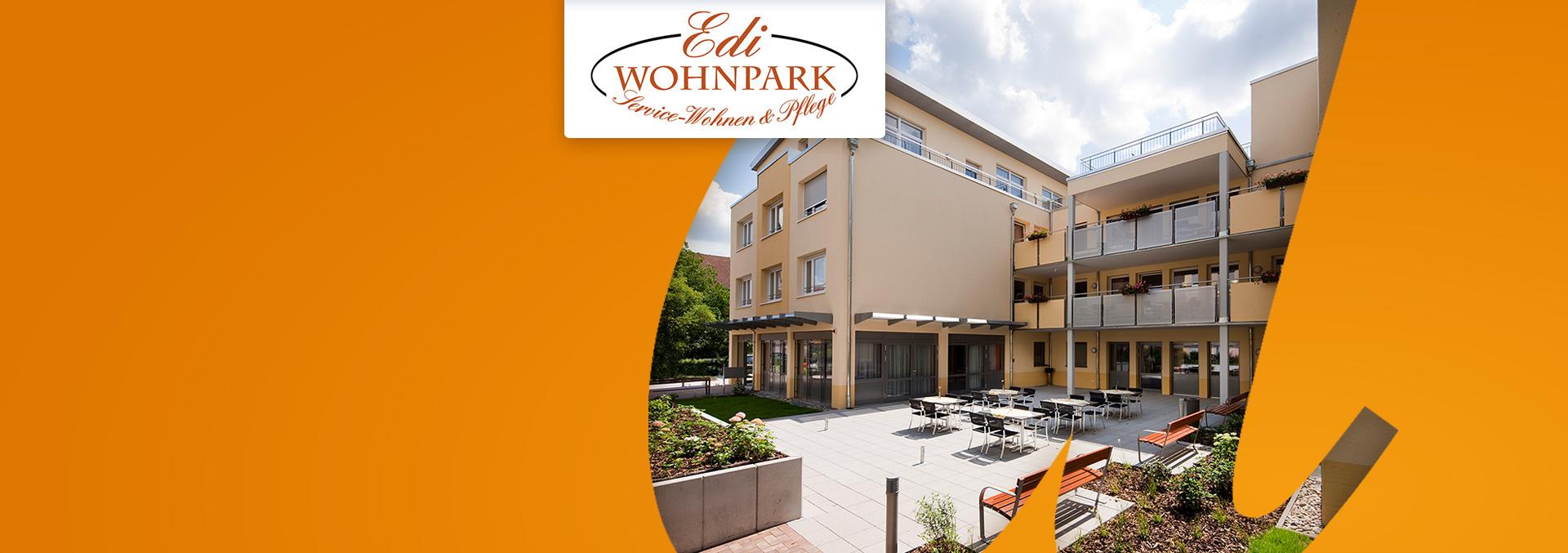 Service-Wohnen und Pflege Edi-Wohnpark: Terrasse mit weißen Tischen, schwarzen Stühlen, roten Bänken und Bepflanzung, die Sonne scheint.