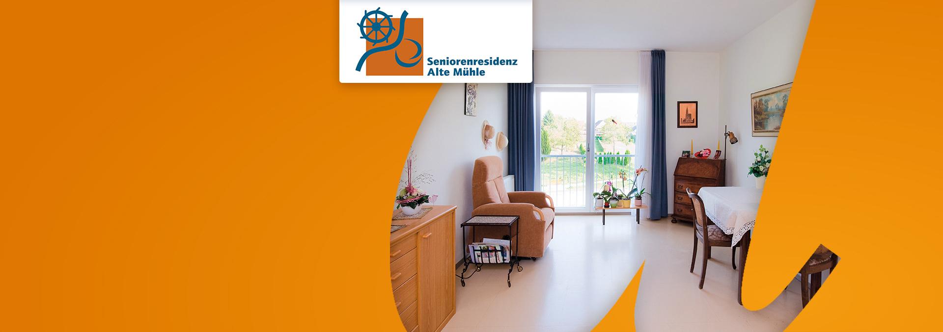 Wohnen in der Seniorenresidenz ALTE MÜHLE: Helles Zimmer mit Blick ins Grüne, gemütlich eingerichtet mit Sessel, Holzmöbeln und Bildern.
