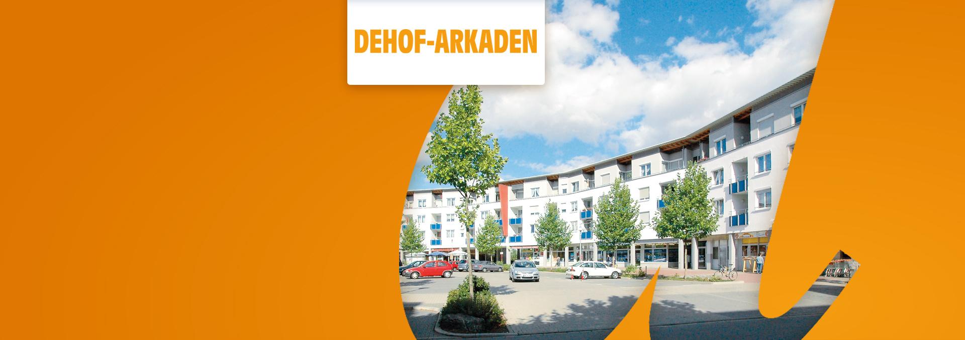 Service-Wohnanlage DEHOF-ARKADEN von außen, vierstöckige Gebäude rund um einen großen Parkplatz gebaut, im Erdgeschoss sind Geschäfte untergebracht.