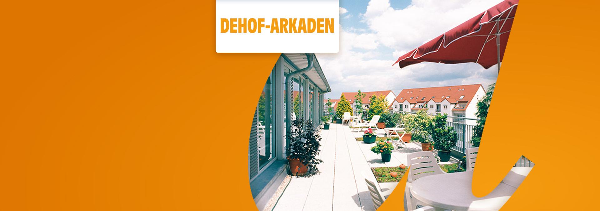Service-Wohnanlage DEHOF-ARKADEN Terrasse vor einer Glasfront mit weißen Sitzmöbeln, rotem Sonnenschirm, zahlreichen Topfpflanzen.