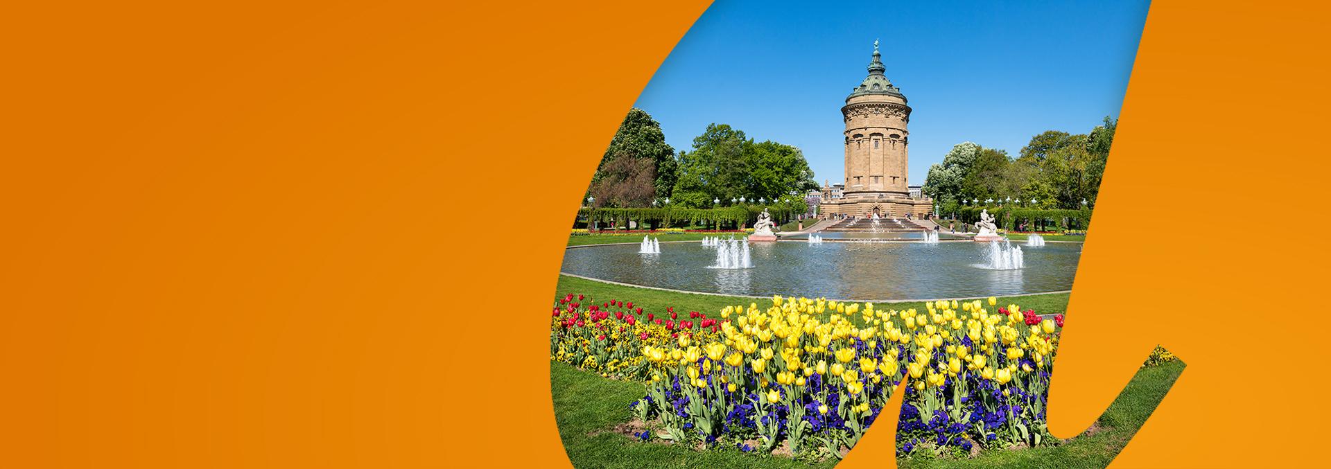 Services in Mannheim: Das Wahrzeichen Mannheims, der Wasserturm, fotografiert über ein Blumenbeet und eine Brunnenanlage