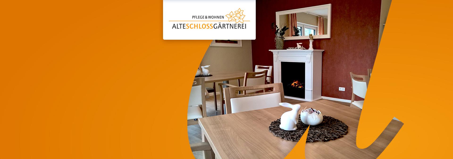 Pflege und Wohnen Alte Schlossgärtnerei, Speiseraum mit Sitzmöbeln und Parkett aus mittel-hellem Holz, Porzellanhasen und -eiern auf den Tischen, an der Wand eine Kaminattrappe.