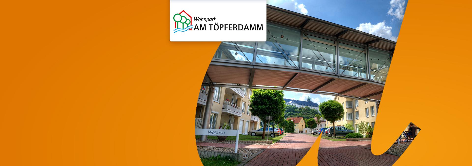 Wohnen im Wohnpark AM TÖPFERDAMM: Eingangsbereich außen mit Überführung und begrünten Parkplätzen