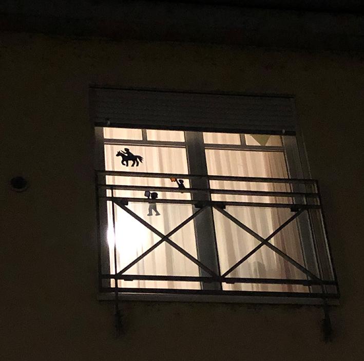 Von außen, im Dunkeln, sieht man gut zwei Fensterbilder an den von innen beleuchteten Fenstern.