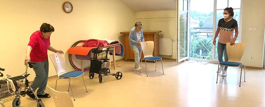 Zwei Bewohnerinnen halten sich an einem Stuhl fest und heben ein Bein. Eine Mitarbeiterin leitet sie an.