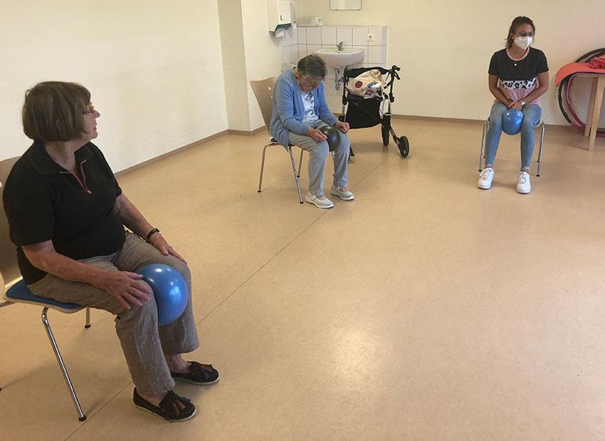 Zwei Bewohnerinnen und eine Mitarbeiterin sitzen auf Stühlen und halten jeweils einen Ball zwischen den Knien fest.