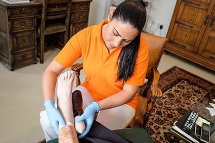 Eine Mitarbeiterin verbindet das Bein einer Kundin.