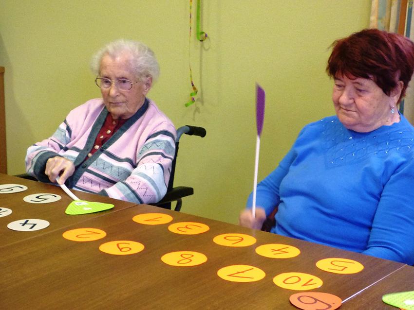 Zwei Seniorinnen halten Fliegenklatschen in der Hand, auf dem Tisch vor ihnen liegen Zahlen-Karten.